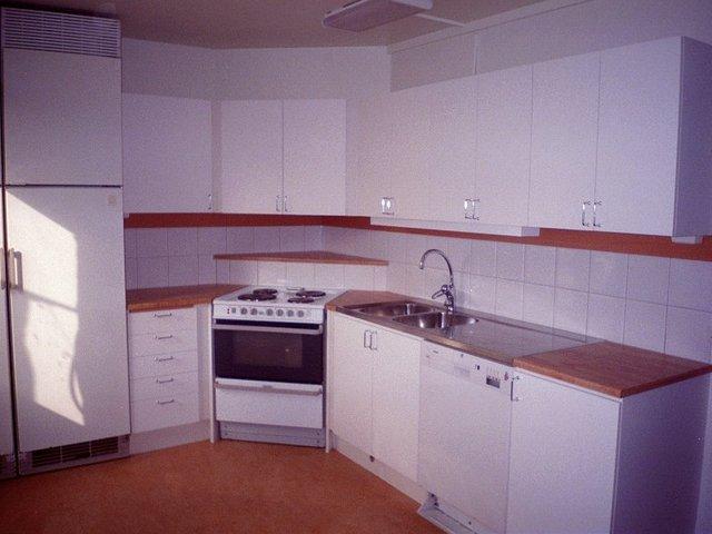 spoře vybavená kuchyň v bílé a hnědé barvě.jpg